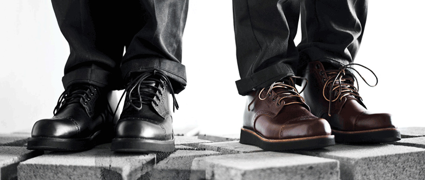 Close up of two men standing side by side on cinder blocks, wearing black and brown leather boots