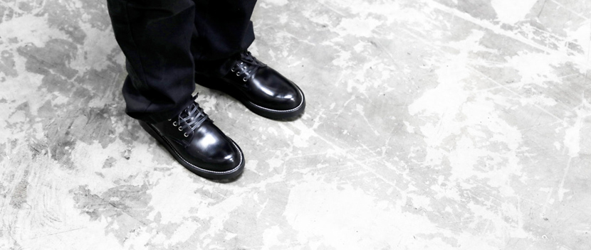 Ankle view of a man wearing black polished leather michael oxford shoes standing on a white distressed concrete floor